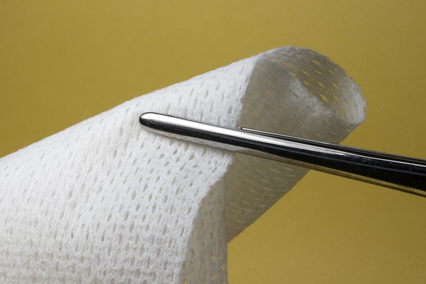 Medical tweezers holding gauze.