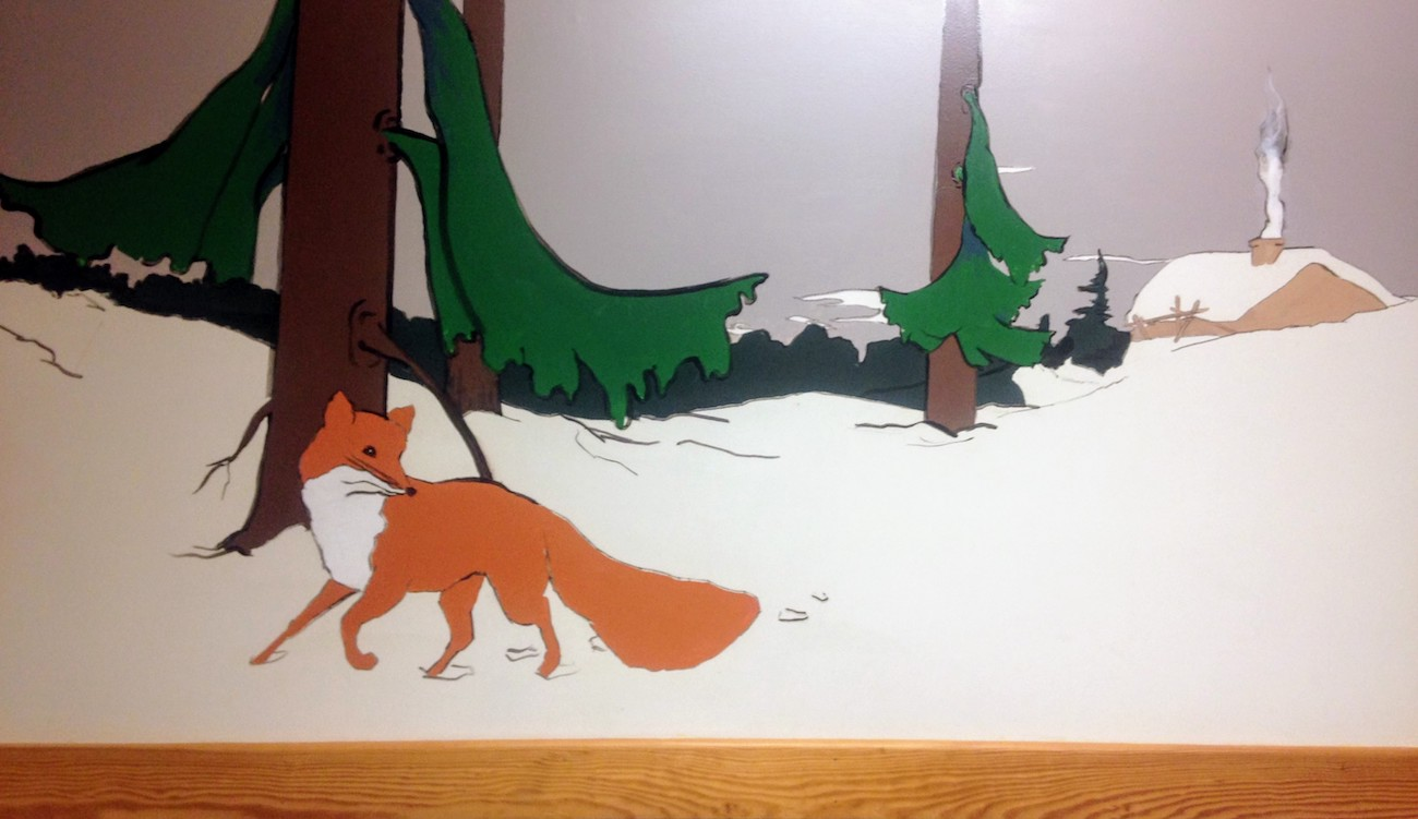 Mural of a grown fox in snowy pine woods looking over its shoulder.