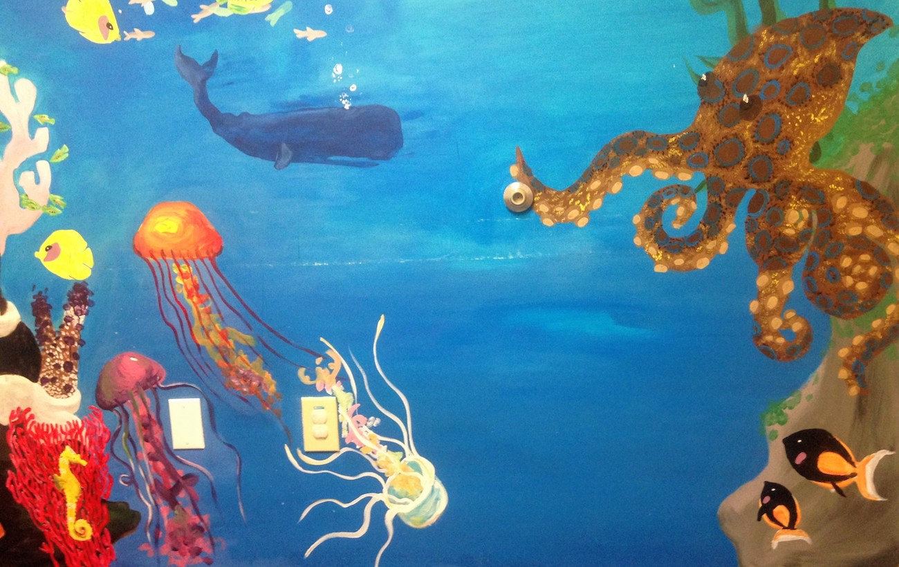 Mural of an ocean scene, with a brown, blue-spotted octopus, multi-colored jellyfish, a yellow seahorse, and other aquatic animals near some coral.
