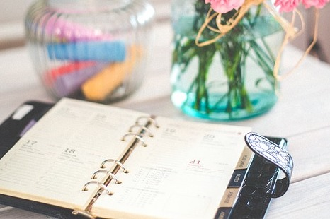 A daily planner open on a table near some colorful jars and vases.